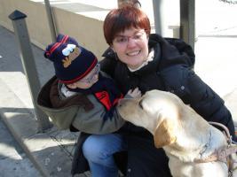 une femme avec un bébé et son chien guide